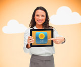 Businesswoman pointing to weather app symbol on tablet