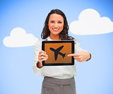 Woman standing holding a tablet pc showing a plane symbol