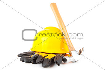 Claw hammer leaning against hard hat and builder's gloves