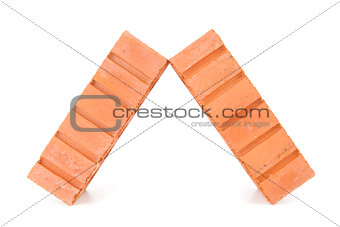 Two clay bricks leaning against each other
