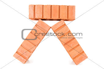 Three clay bricks being piled