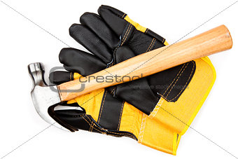 Hammer lying on two leather gloves