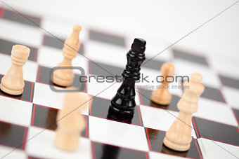Black queen surrounded by white chess pieces