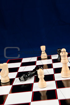 Black queen lying at the chessboard