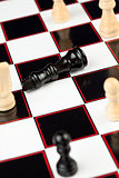Black queen lying at the chessboard while white standing
