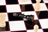 Black chessman lying