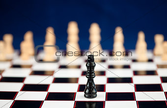 One black chessman standing at the chessboard