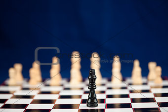 Black chess piece standing at the chessboard
