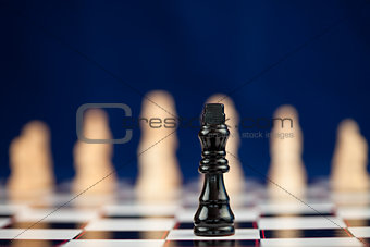 Black chess piece standing at the chessboard white ones behind