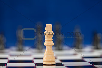 White queen standing at the chessboard while black ones standing behind