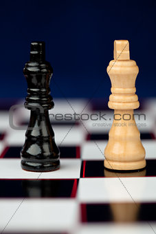 Black and white queen standing at the chessboard against blue background