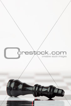 Black chessman lying at the chessboard