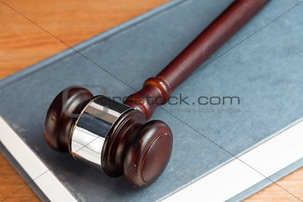 Gavel on a blue book on desk