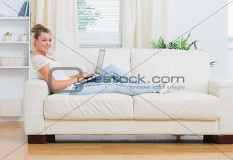 Blonde woman working on laptop on the couch