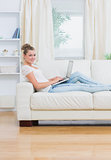 Woman using laptop lying on the couch
