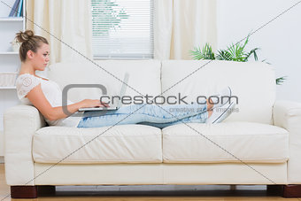 Blond woman looking at the laptop on the couch