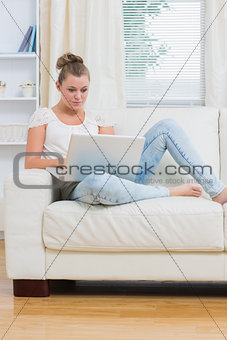 Woman typing on laptop while relaxing