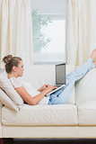 Woman typing on the laptop while relaxing