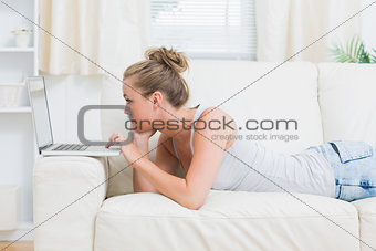Woman typing on the laptop while lying on the sofa