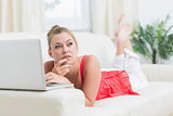 Woman looking thoughtful while using laptop