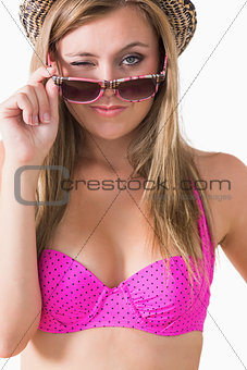Blonde winking while holding sunglasses and wearing bikini
