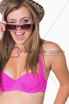 Woman holding her glasses while winking