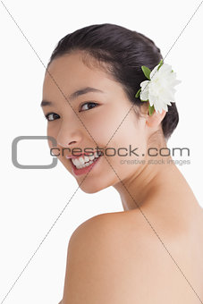 Cheerful woman wearing a flower in hair