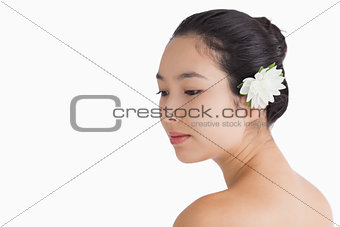 Woman wearing a flower in hair and looking away