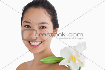 Joyful woman having a flower on her shoulder