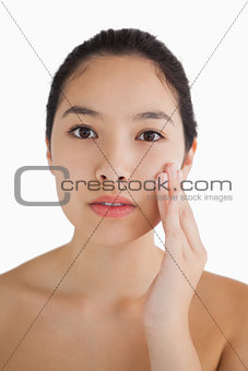 Black haired woman touching her face