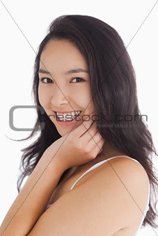 Woman smiling while touching her skin