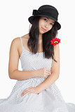 Woman holding flower in a polka dot dress