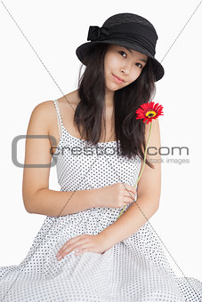 Woman holding flower in a polka dot dress