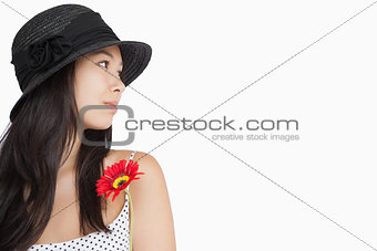 Cheerful woman with flower looking away wearing a hat