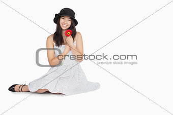 Woman with flower in dress sitting on floor