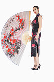 Woman in kimono standing with large silk fan