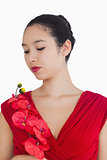 Woman wearing a red dress holding a red orchid
