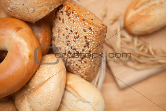 Bread in the basket with a roll on a wooden board