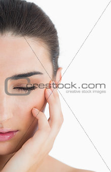 Woman having eyes closed while touching her cheek