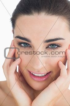 Woman touching her cheek while smiling