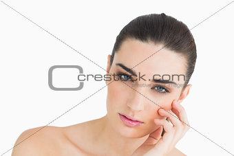 Pale looking woman touching her face