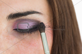 Pale woman getting smoky eyes