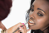 makeup artist applying golden lip gloss