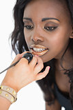 Woman getting golden lip gloss applied