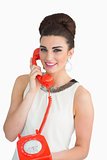 Woman dressed in sixties style holding an old phone