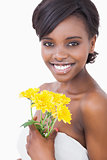 Woman smiling holding yellow flowers
