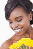 Woman smiling while holding yellow flowers