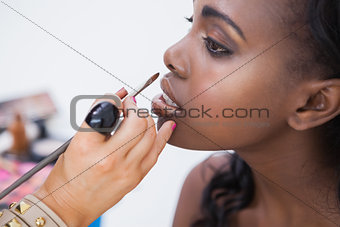 Woman sitting getting lip-glosss put on