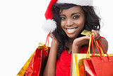 Festive woman standing looking while holding bags