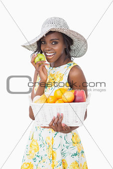Woman holding a fruit basket and an apple